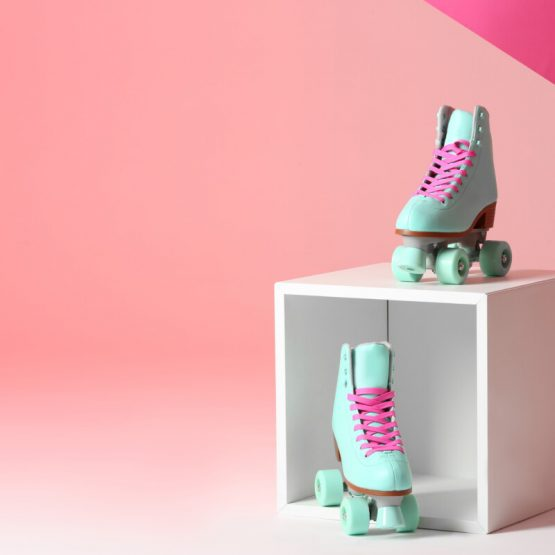 Pair of vintage roller skates and storage cube on color background. Space for text